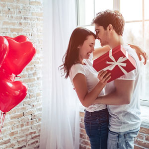 saint valentine's day gift and red, heart-shaped balloons